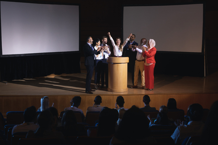 Front view of happy Caucasian businesswoman standing at the stage of the auditorium with colleagues in front of audience 免版税图像