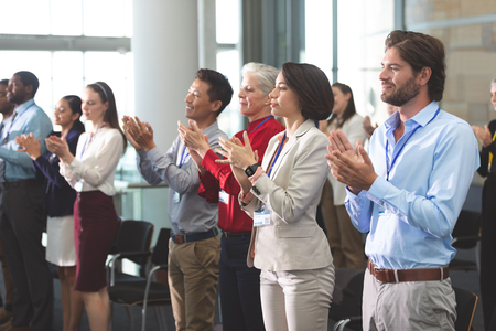 Side view of diverse business people applauding standing at a business seminar in office building Stok Fotoğraf
