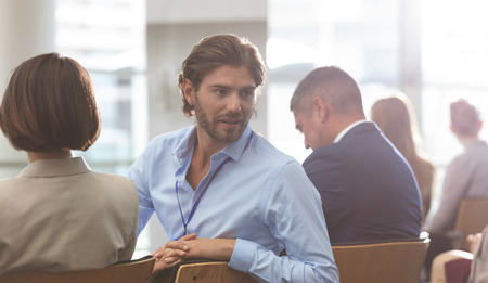 Rear view of young Caucasian businessman interacting with his colleague during seminar in office building