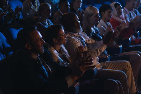 Side view of mixed race business colleagues sitting and watching presentation with audience and clapping hands Imagens