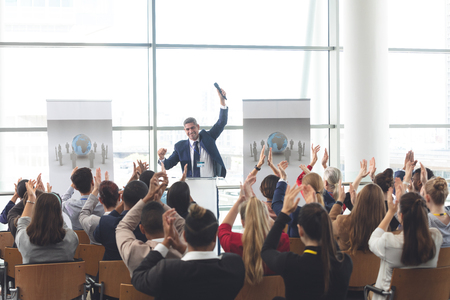 Rear view of diverse business people applauding and celebrating while they are sitting in front of mixed race businessman at business seminar in office building