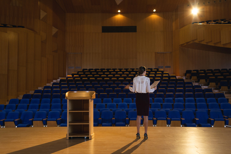 Rear view of blonde Caucasian businesswoman practicing and learning script while standing in the auditorium Banco de Imagens