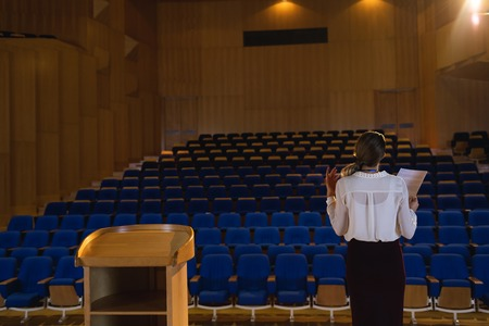 Rear view of blonde Caucasian businesswoman practicing and learning script while standing in the auditorium