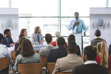 Vorderansicht eines afroamerikanischen Geschäftsmanns, der in einem Business-Seminar in einem modernen Bürogebäude spricht
