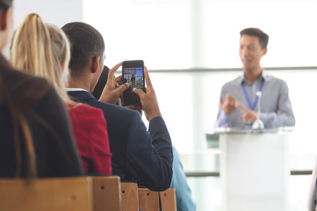Rear view of African-american businessman taking photo of Asian businessman with mobile phone during seminar in office building