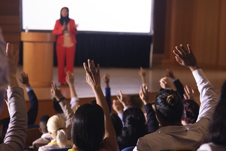 Front view of mixed race businesswoman standing around the podium in the auditorium while audience raising hand for asking question 写真素材