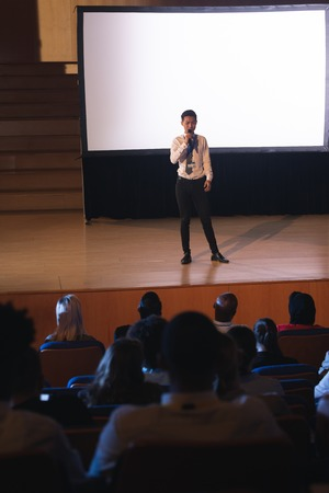 High view of young Asian businessman standing and giving presentation in auditorium while holding mike in his hand in auditorium
