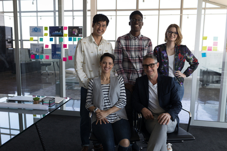 Portrait of mixed race business people posing together in modern office. They seem happy