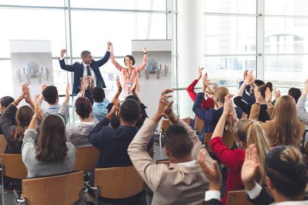 Rückansicht verschiedener Geschäftsleute, die applaudieren und feiern, während sie beim Geschäftsseminar im Bürogebäude vor multiethnischen Geschäftsleuten sitzen Standard-Bild