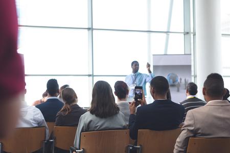 Achteraanzicht van jonge Afro-Aericaanse zakenman die op foto klikt met mobiele telefoon in een zakelijk seminar