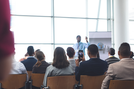 Rear view of young African-Aerican businessman clicking photo with mobile phone in a business seminar