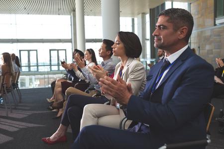 Zijaanzicht van diverse zakenmensen die klappen tijdens een zakelijk seminar in een kantoorgebouw Stockfoto