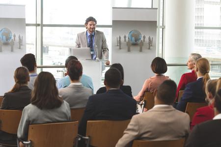 Vorderansicht des kaukasischen Geschäftsmannes mit Laptop spricht vor einer vielfältigen Gruppe von Geschäftsleuten, die beim Geschäftsseminar im Bürogebäude sitzen