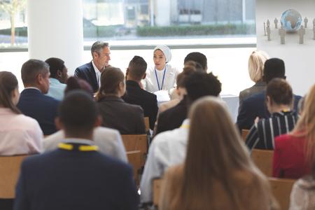 Rückansicht einer Gruppe verschiedener Geschäftsleute, die an einem Geschäftsseminar im Bürogebäude teilnehmen Standard-Bild