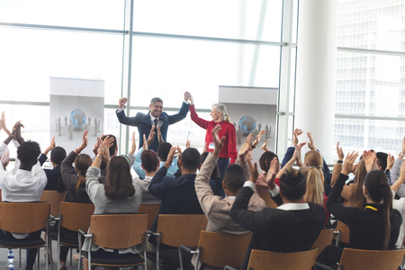 Rear view of diverse business people applauding and celebrating while they are sitting in front of mixed race and Caucasian business people at business seminar in office building