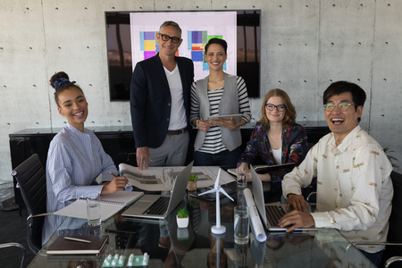 Portrait of mixed race business people in a conference room at modern office. They seem happy