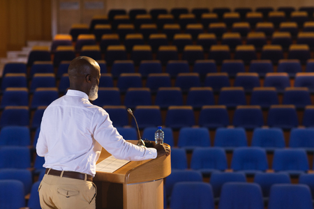 Side view of matured African-American businessman practicing for speech in the empty auditorium Foto de archivo