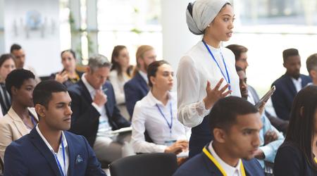 Vista laterale di una giovane imprenditrice di razza mista che fa domande durante il seminario nell'edificio degli uffici