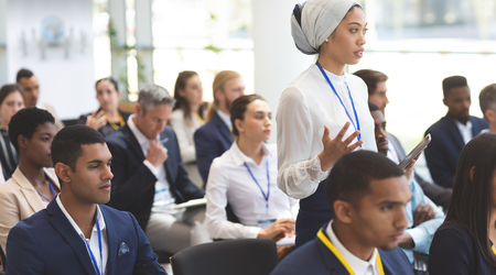 Zijaanzicht van jonge zakenvrouw van gemengd ras die vraag stelt tijdens seminar in kantoorgebouw