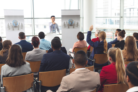 Rear view of Caucasian businessman raising hand while he is sitting in front of Asian businessman at business seminar in office building