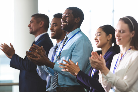Side view of happy diverse business people applauding standing at a business seminar in office building Imagens