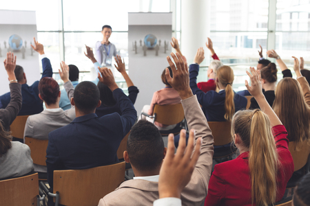 Rear view of diverse business people raising hands while they are sitting in front of Asian businessman at business seminar in office building Foto de archivo