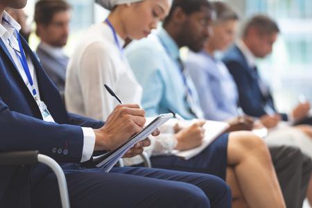 Mittlerer Abschnitt des kaukasischen Geschäftsmannes, der während des Seminars im Bürogebäude auf Notizblock schreibt Standard-Bild