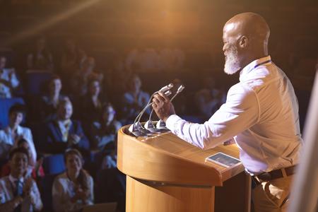 Seitenansicht eines alten afroamerikanischen Geschäftsmannes, der in der Nähe des Podiums steht und dem Publikum im Auditorium eine Rede hält
