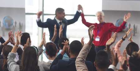 Rear view of diverse business people applauding and celebrating while they are sitting in front of mixes race and Caucasian business executives at business seminar in office building