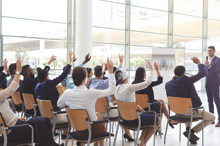 Rückansicht einer Gruppe verschiedener Geschäftsleute, die Hände heben, während sie auf der Konferenz einem hübschen gemischten Geschäftsmann zuhören