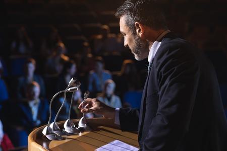Side view of Caucasian businessman holding podium speaker in his hand at auditorium
