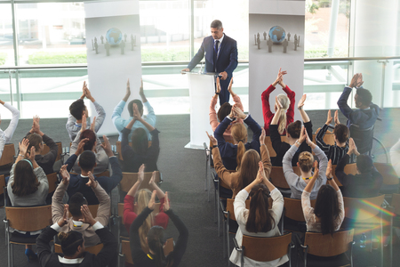 High angle view of diverse business people applauding while they are sitting in front of mixed race businessman at business seminar in modern office building Standard-Bild