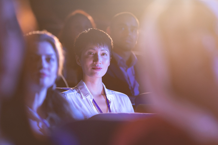 Front view of beautiful Asian businesswoman sitting in the auditorium and looking at camera