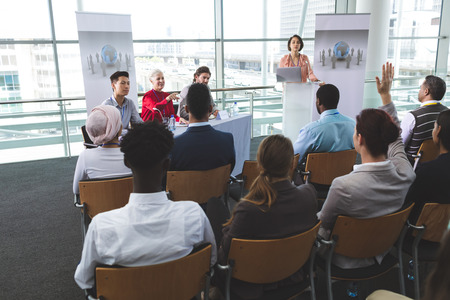 Rear view of businesswoman raising hand in a business seminar while mixed-race businesswoman speaks in office building
