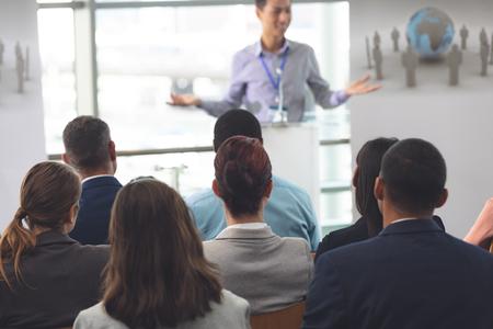 Rückansicht einer vielfältigen Gruppe von Geschäftsleuten, die an einem Seminar mit einem asiatischen Geschäftsmann teilnehmen, der im Bürogebäude spricht