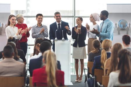 Vista frontal de un grupo diverso de profesionales de negocios de pie en el podio mientras habla frente a la gente de negocios en el seminario de negocios en el edificio de oficinas Foto de archivo