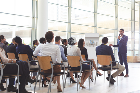 Front view of handsome mixed-race businessman speaking at business seminar with diverse business people listening to him at conference