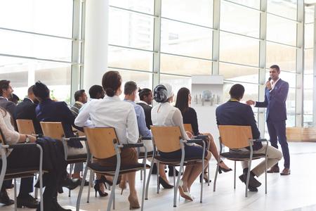 Vooraanzicht van een knappe zakenman van gemengd ras die spreekt op een zakelijk seminar met diverse zakenmensen die naar hem luisteren op een conferentie