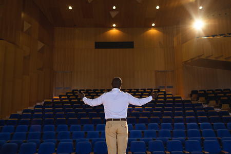 Rear view of old African-American businessman with arm stretched out standing in a auditorium