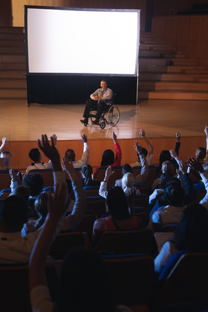 High view of Caucasian businessman sitting on a wheelchair and giving presentation to the audience while audience raising hand for asking question in auditorium 写真素材