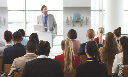 Rear view of group of diverse business people listening to a Caucasian businessman speak at seminar in modern office