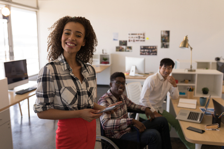 Front view of young diverse business colleagues working together in modern office. They seem happy Imagens