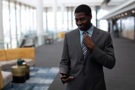 Vista frontal del joven empresario afroamericano mediante teléfono móvil de pie en la oficina moderna. El está sonriendo