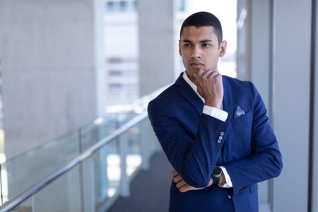 Vooraanzicht van een bedachtzame jonge zakenman van gemengd ras met de hand op de kin die wegkijkt terwijl hij in een modern kantoor staat Stockfoto
