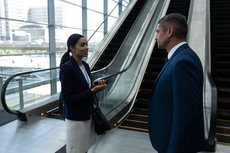 Side view of businessman and businesswoman interacting with each other near escalator in office