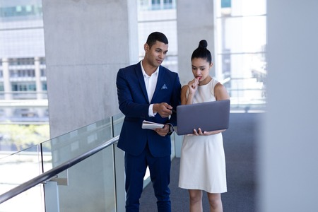 Front view of young mixed-race business people discussing over laptop standing in modern office