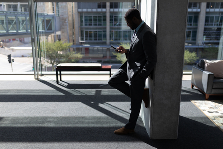 Side view of young African-American businessman leaning against wall and using mobile phone in modern office