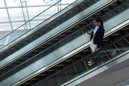 Mixed-race businesswoman using mobile phone while moving down on escalator in office Stock Photo
