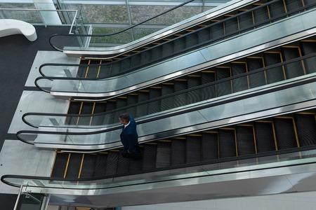 High angle view of Caucasian businessman talking on mobile phone while moving down on escalator in office