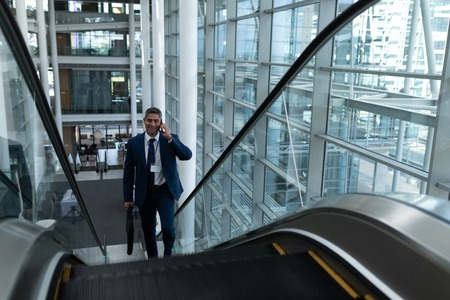 Front view of Caucasian businessman talking on mobile phone while moving up on escalator in office